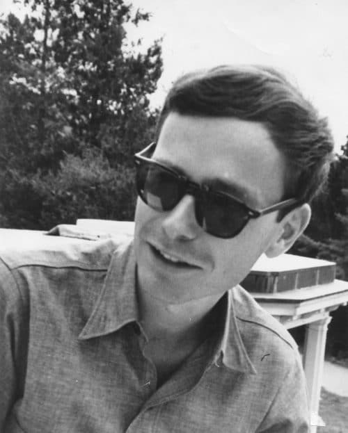 Black and white photo of a young man with short brown hair wearing sunglasses and a collared shirt. He is smiling and standing in front of a tree.